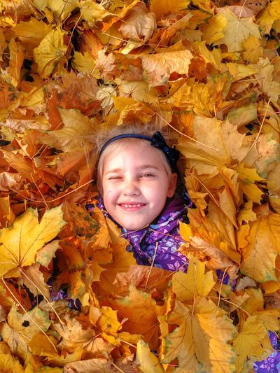 Portrait Of Happy Girl Covered In Leaves During Autumn