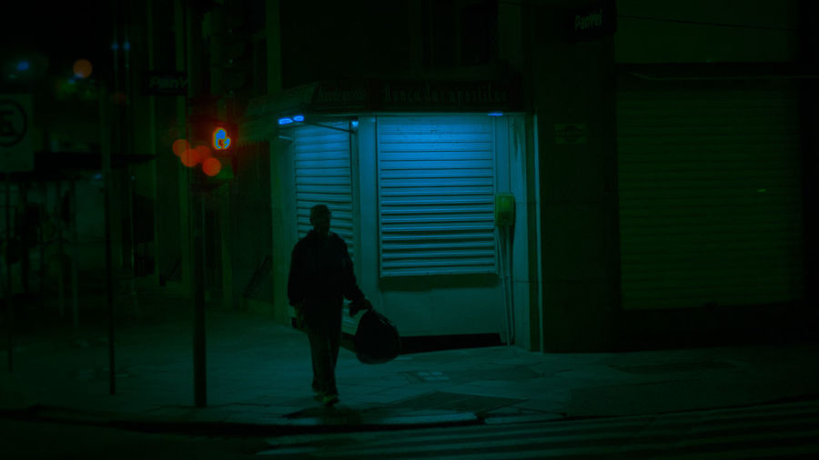 Rear view of silhouette man walking in illuminated city at night
