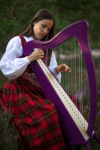 Young woman playing harp at forest
