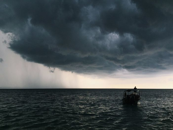 Man sailing boat in ocean against storm clouds