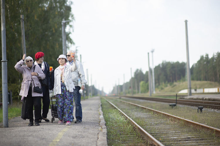 People standing on railroad track against sky