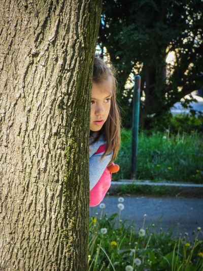 Portrait of happy girl on tree trunk