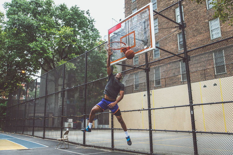 Young man scoring goal at basketball court
