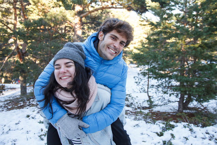 Smiling Young Woman Giving Piggyback To Boyfriend On Field During Winter