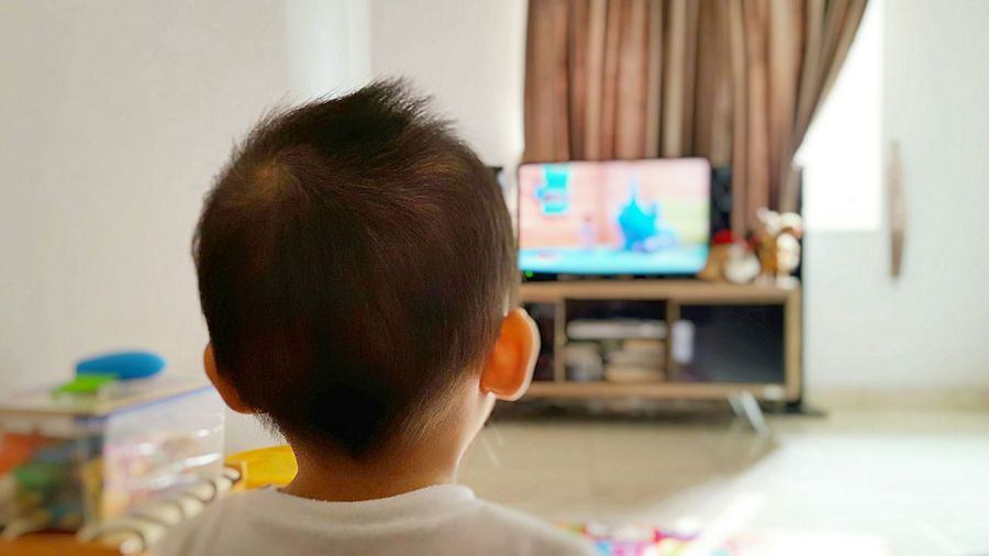 Close-Up Of Young Boy Watching Tv