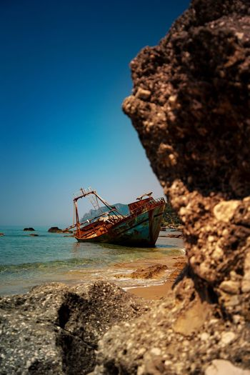 Low angle view of abandoned ship on beach against clear sky