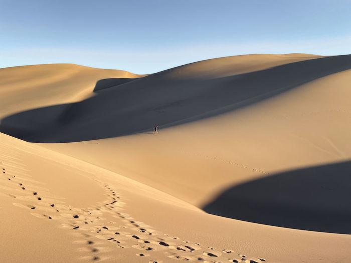 Distant view of man walking on desert against sky