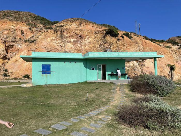 House on mountain against clear blue sky