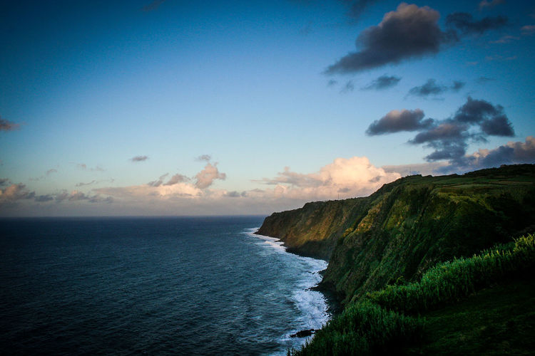 Grassy mountain by sea against sky at azores