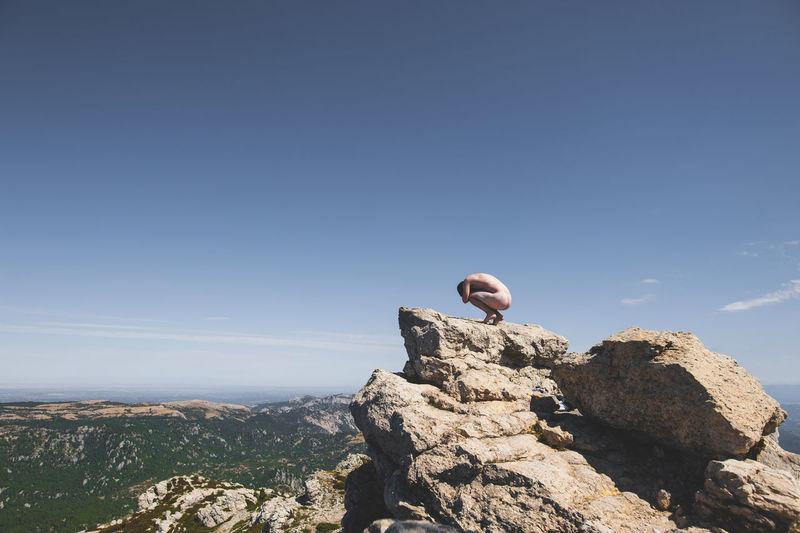 Naked man on cliff