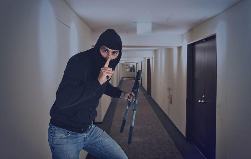Portrait of burglar holding work tool standing in corridor