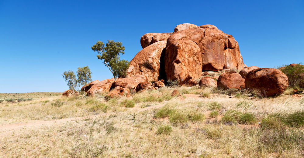 Rock formations on field against clear blue sky