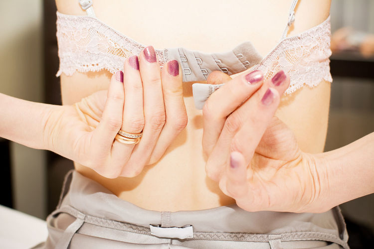 Midsection of woman wearing bra at home