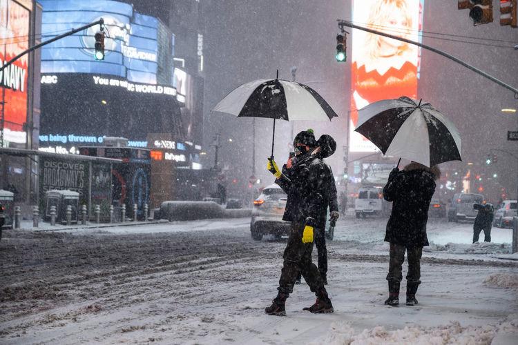 People walking on wet street during winter