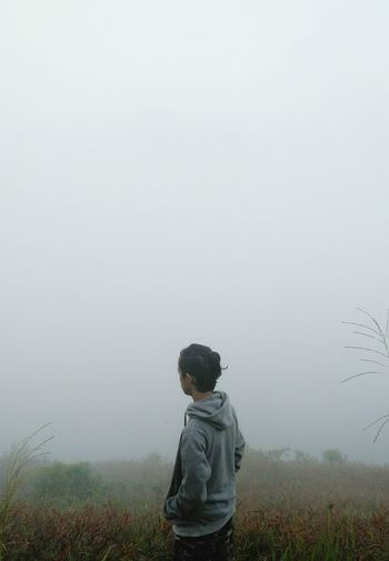 Rear View Of Man Standing On Field Against Sky During Foggy Weather