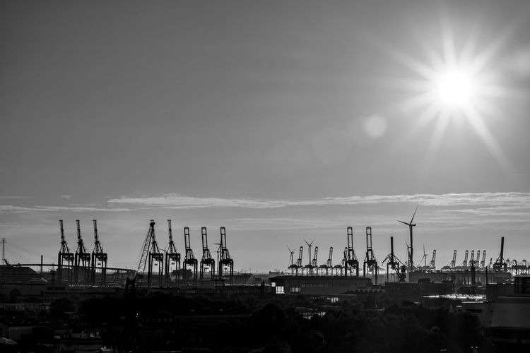 Cranes at harbor against sky during sunny day