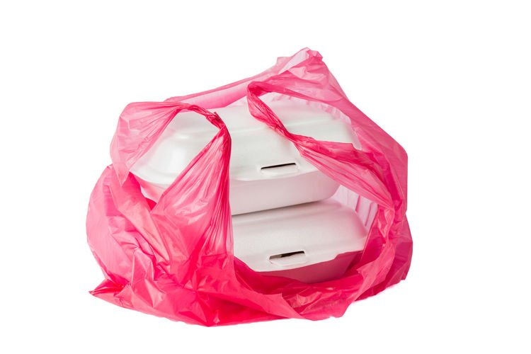 Close-up of white boxes in pink plastic over white background