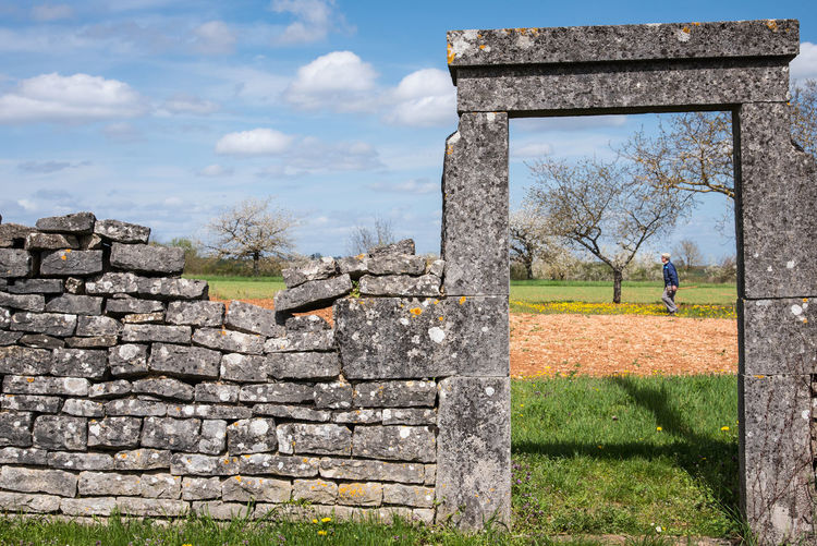 Stone Material Stone Wall The Past Men One Person Spring Springtime Door Wall Garden Gardening Gardener History Architecture Sky Nature Grass Day Travel Destinations Field Tourism Old Ruin Built Structure Ancient Travel Plant Old Land Cloud - Sky Outdoors Ancient Civilization