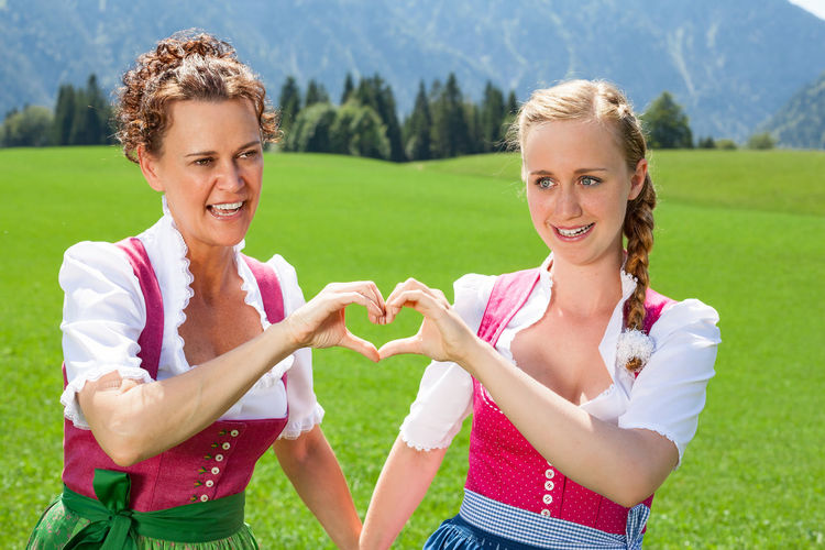 Portrait of happy young woman making heart shape while standing on field