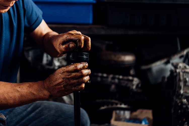 Auto Repair Shop Business Focus On Foreground Hand Holding Human Body Part Human Hand Indoors  Industry Mechanic Men Occupation One Person Repairing Skill  Technician Working Workshop