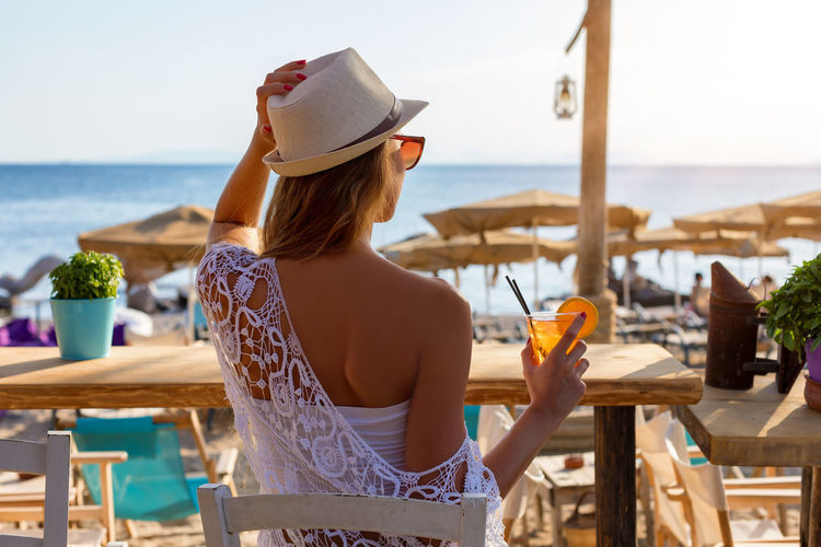 Rear view of woman with drink sitting on chair near beach