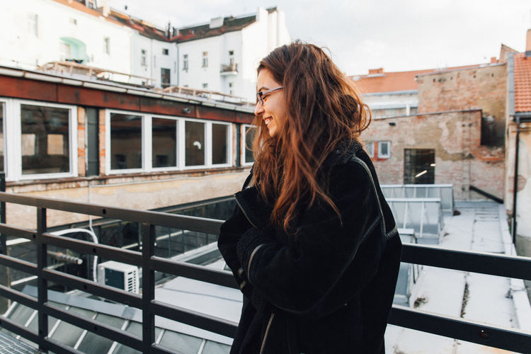 Young woman looking away while standing against railing
