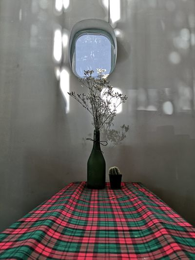 Illuminated electric lamp on table by window