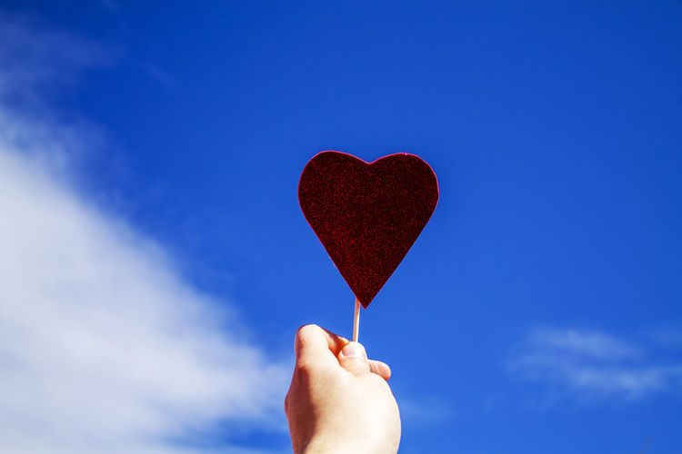 Cropped Hand Of Person Holding Heart Shape Candy Against Sky