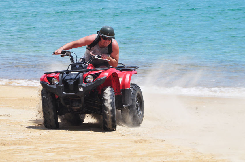 Tourist riding quad bike on beach at Lang Co, Vietnam. Action Activities Beach Crouching Editorial  Land Vehicle Leisure Lifestyles Lăng Cô Men Muscles Quad Bikes Riding Sand Sea Shore The Color Of Sport Tourism Tourist Travel Turning Vacations Vietnam Water
