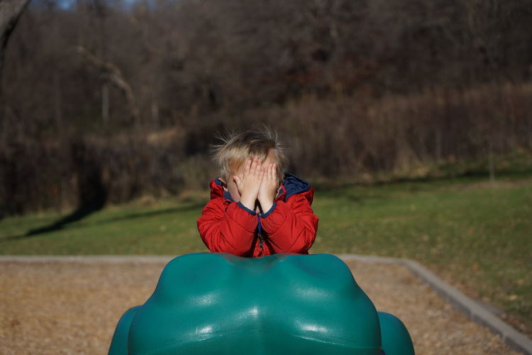 Boy Hiding Face At Playground