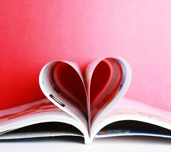 Close-up of heart shape made with pages on table against red wall
