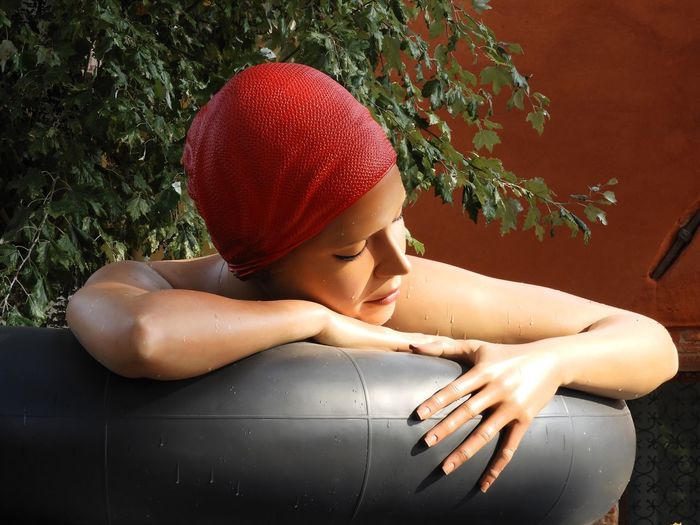 Woman Relaxing In Bath Tub Against Plants