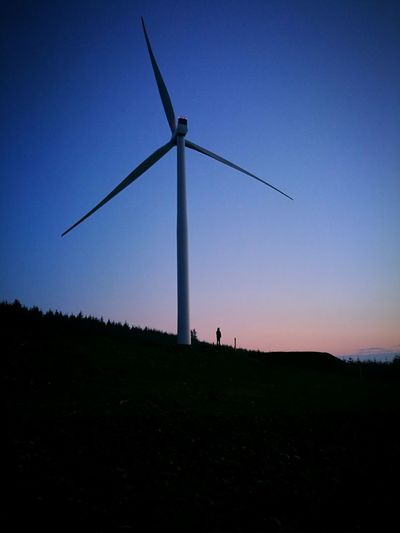 Silhouette of wind turbines on field against clear sky