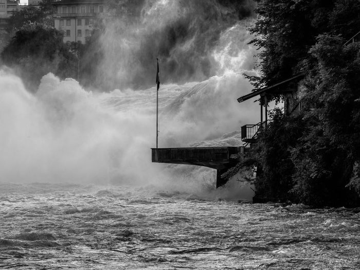 dawn of the raging waters Gry Et L'aventure Cascade Rheinfall Blackandwhite Monochrome EyeEm Nature Lover Spectacular Majestic Natural Landmark Dramatic Landscape Betterlandscapes Scenics Beauty In Nature Morning Riverside Riverview White Water Spray Flag Flagpole Silhouette Platform Viewing Platform Tourist Attraction  Tourism Water Sky Power In Nature Flag Pole Shore