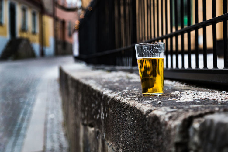 Close-up of beer glass on retaining wall