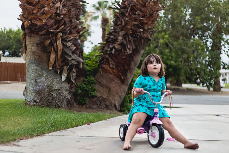 Full Length Of Girl Riding Tricycle On Footpath