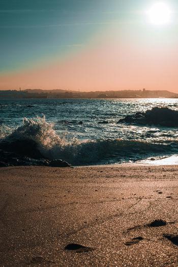 Sea waves rushing towards shore during sunset