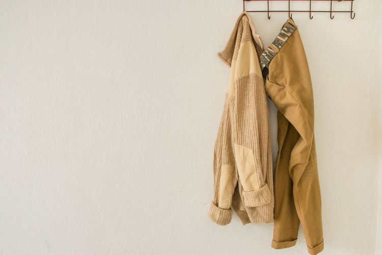 Close-Up Of Clothes Hanging Against Wall