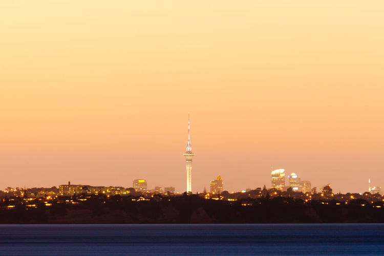 Distant skyline of Auckland City, New Zealand, with Sky Tower illuminated in twilight dusk after sunset City Cityscape Auckland Auckland City Auckland, New Zealand New Zealand Sky Tower Sky Tower Auckland TV Tower Sunset Skyline Illuminated Twilight Distant Citylights Dusk Architecture Downtown Glowing Metropolis Modern Ocean Urban Highriser Skyscraper Built Structure Sky Tower Building Exterior Travel Destinations Travel Tall - High Tourism No People Water Building Office Building Exterior Spire