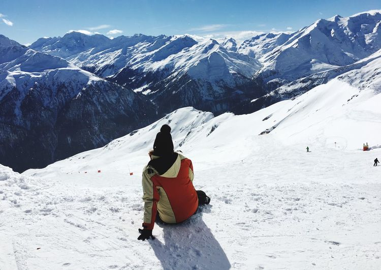 Rear view of person sitting on snowcapped mountain during sunny day
