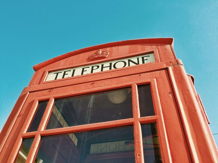 Low angle view of red telephone booth