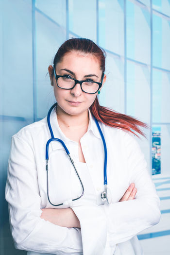 young She doctor Hospital Portrait Eyeglasses  Lab Coat Responsibility Doctor  Young Women Women Occupation Looking At Camera Scrubs Surgeon Emergency Room Medical Occupation International Women's Day 2019