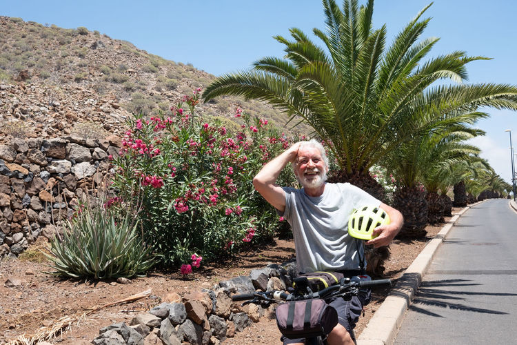Happy senior man athlete resting on his bike. Yellow helmet. One adult people. Blue sky. Mountain and palm trees on background Active Activity Adult Aged Background Beard Beautiful Bicycle Bike Biking Blue Sky Bright Casual Caucasian Elderly Enjoying Excursion Exercise Exercising Fitness Happiness Happy Having Fun Healthy Helmet Holiday Lifestyle Light Man Morning Mountain Range Nature Old One Person Palm Tree People Recreation  Retirement Ride Senior Smiling Sport Street Summer Sunlight Vacation Vegetation Wellness White Hair Workout