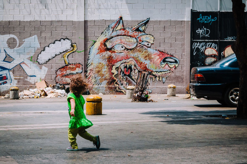 Lobo Feroz The Art Of Street Photography City Graffiti Architecture Art And Craft Creativity Building Exterior Street Built Structure Day Full Length Transportation Mode Of Transportation Representation One Person Road Street Art City Life Text Real People Wall - Building Feature Outdoors Mural EyeEm Best Shots EyeEm Selects The Street Photographer - 2019 EyeEm Awards