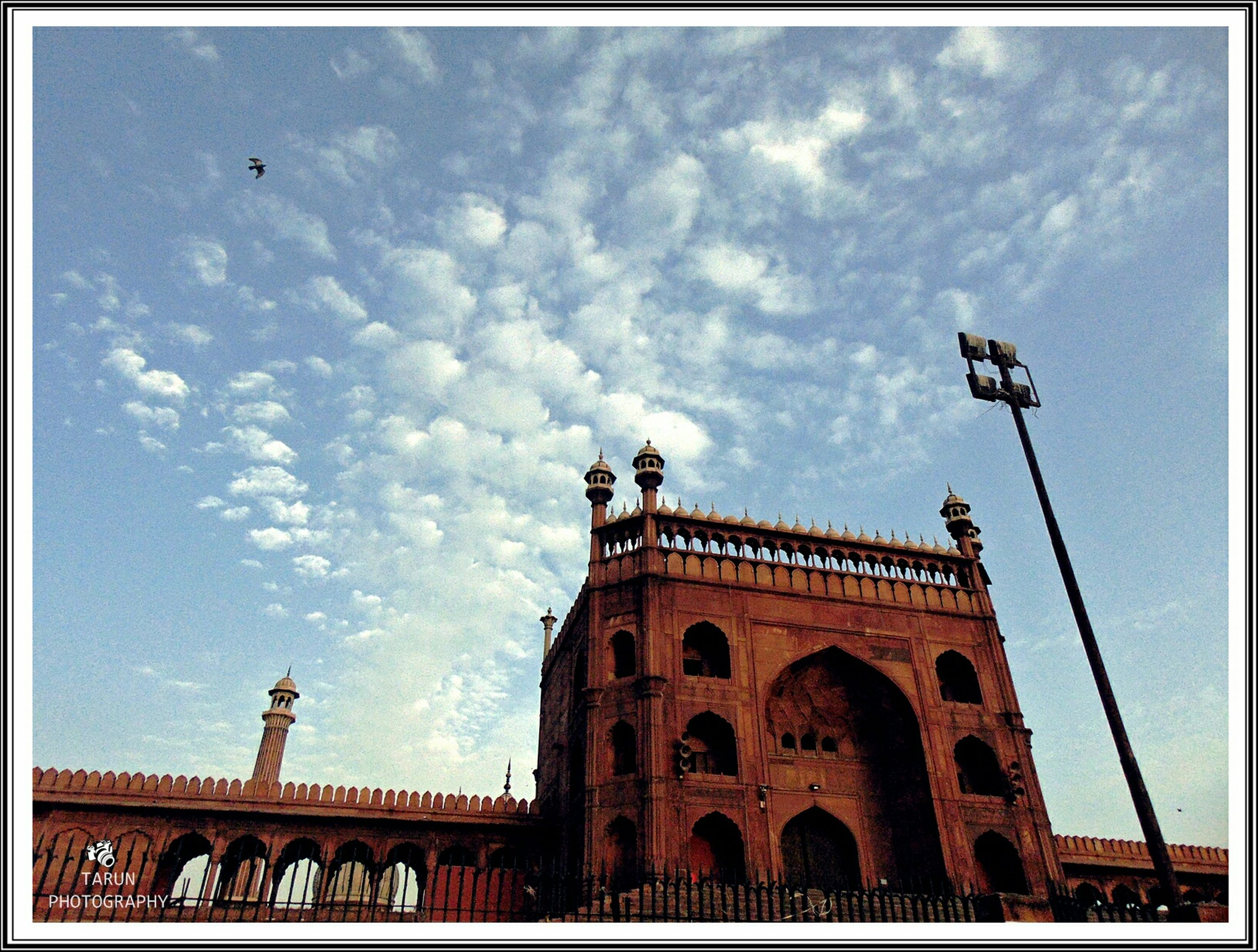 low angle view, architecture, built structure, sky, building exterior, transfer print, religion, church, place of worship, arch, high section, cloud - sky, auto post production filter, spirituality, cloud, history, travel destinations, outdoors