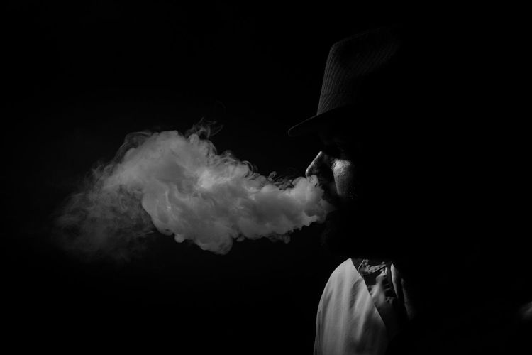 Side view of young man smoking against black background