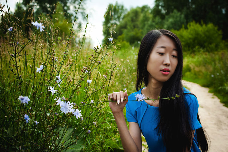 Close-up of young woman by flowering plants in forest