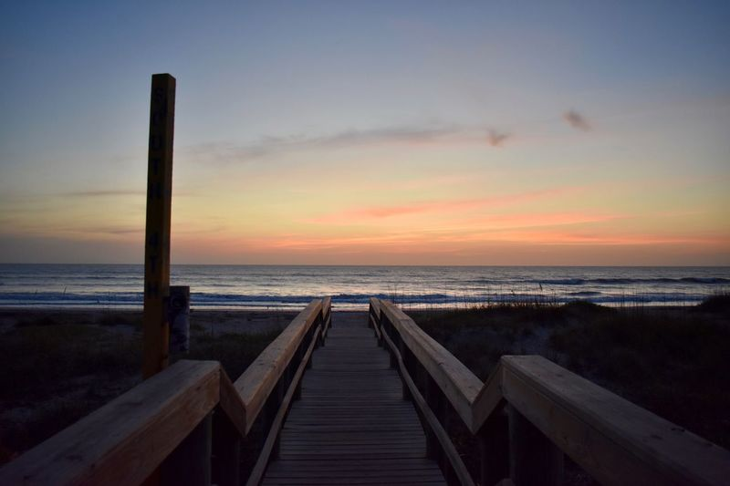 Wooden benches on beach against sky during sunset