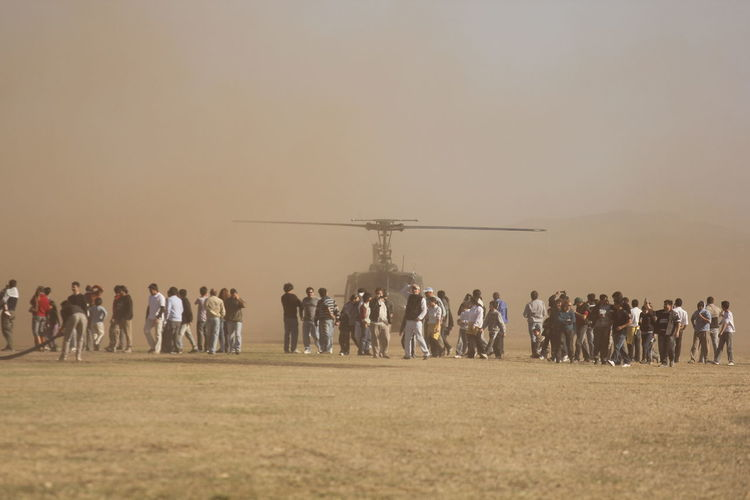 People by helicopter on land against sky