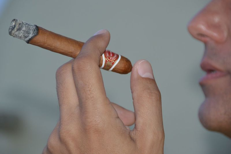 Cigar Cigar Smoking Holding Human Finger Human Hand Lifestyles Part Of Real People Romeo And Juliet